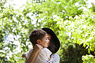 Mother and son hugging outdoors - VABF000533