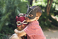Mother and little son with animal masks playing in the park - VABF000563