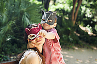 Mother and little son with animal masks playing in the park - VABF000566