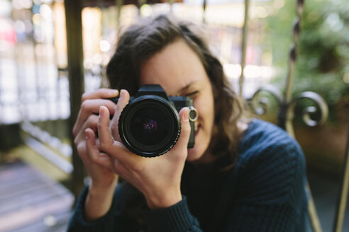 Young woman on balcony using vintage camera - BOYF000384