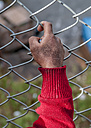 Close-up of hand at mesh wire fence - ALR000517