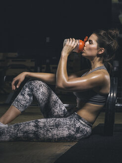 Female athlete sitting and drinking, drinking bottle - MADF000968