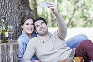 Smiling young couple having a picnic with white wine taking a selfie - ZEF008677