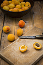 Sliced and whole apricots on wood - LVF004926