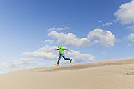 Man running down a sand dune - GWF004733
