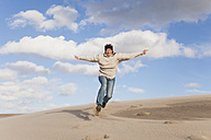 Enthusiastic mature woman running and jumping on sand dune - GWF004736