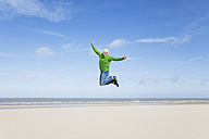 Enthusiastic mature man jumping on beach - GWF004739