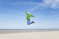 Enthusiastic mature man jumping on beach - GWF004742