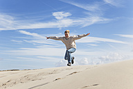 Enthusiastic mature woman jumping over sand dune - GWF004745