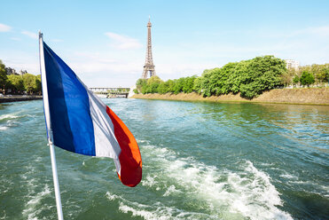 France, Paris, French flag flying over the Seine with Eiffel Tower in the background - GEMF000917