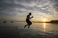Italy, Veneto, Bardolino, Lake Garda, boy jumping into the water at sunset - SARF002737