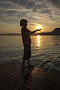 Boy holding hands against the sun at sunset - SARF002740