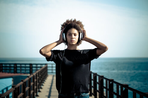 Portrait of serious woman with headphones on a jetty - SIPF000528