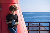 Young woman on deck reading a book - SIPF000531