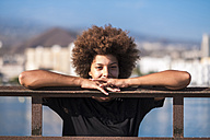 Spain, Tenerife, portrait of young woman leaning on railing - SIPF000534