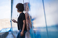 Young woman with headphones and smartphone leaning against wall - SIPF000537