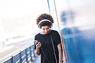 Young woman with headphones and smartphone leaning against wall - SIPF000540