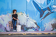 Spain, Tenerife, young woman with rolling suitcase waiting in front of painted wall - SIP000543