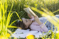 Little girl lying on field of flowers reading a book - SARF002743