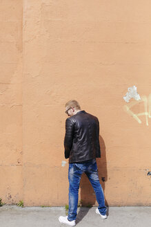 Back view of young man peeing at facade - BOYF000408