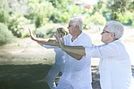 Elderly couple practicing yoga together with instructor - ZEF008694