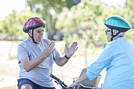 Elderly couple on bicycles talking - ZEF008697