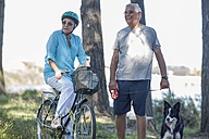 Elderly couple with dog and bicycle in forest - ZEF008703