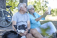 Elderly couple sitting outdoors with dog and digital tablet - ZEF008706