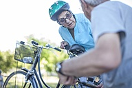 Elderly woman on bicycle talking to man - ZEF008712