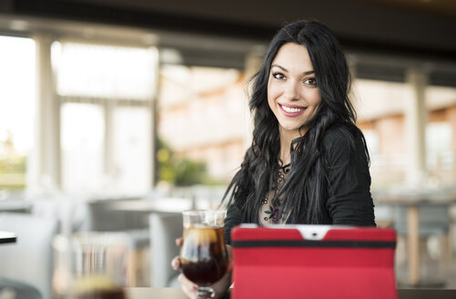 Young woman in cafe using digital tablet - JASF000801