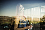 Young woman standing at the window holding drink - JASF000810