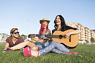 Friends sitting on grass playing guitar - JASF000816