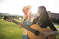 Young women having a drink, playing guitar - JASF000822