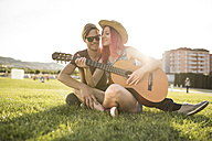 Friends sitting on grass playing guitar - JASF000825