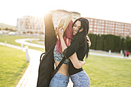 Two young women hugging in park - JASF000831