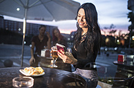 Young woman sitting in bar using smart phone - JASF000855