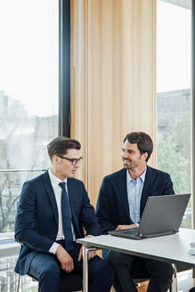 Two businessmen with laptop talking in office - CHAF001768