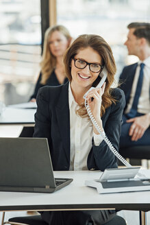 Smiling businesswoman at office desk on the phone - CHAF001789