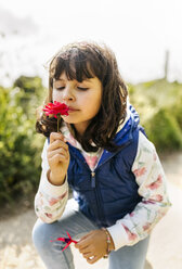 Portrait of little girl smelling red flower - MGOF001928