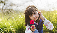 Portrait of little girl with red flower in nature - MGOF001931