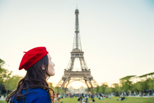France, Paris, Champ de Mars, woman wearing red beret in front of Eiffel Tower looking up - GEMF000920
