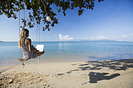 Thailand, woman using laptop on beach - SBOF000002