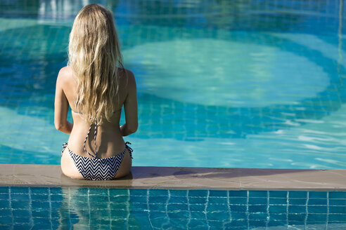 Back view of woman sitting on pool edge - SBOF000005