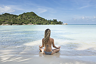 Thailand, woman meditating on beach - SBOF000011