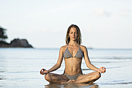 Thailand, woman meditating on beach - SBOF000014