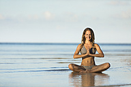 Thailand, smiling woman meditating on beach - SBOF000017