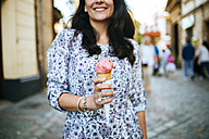 Woman holding strawberry ice cream cone - KIJF000411