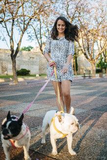 Woman walking her two dogs - KIJF000417