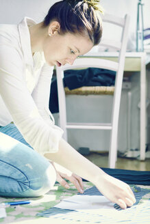 Young woman crouching on the floor at home putting stencil on fabric - SEGF000573