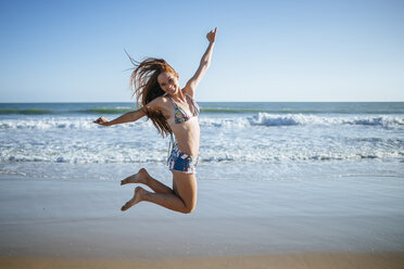 Enthusiastic young woman jumping on beach - KIJF000418